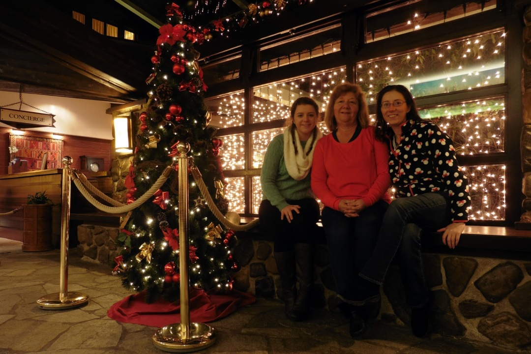 Family photo by Christmas decorations at Disney's Sequoia Lodge