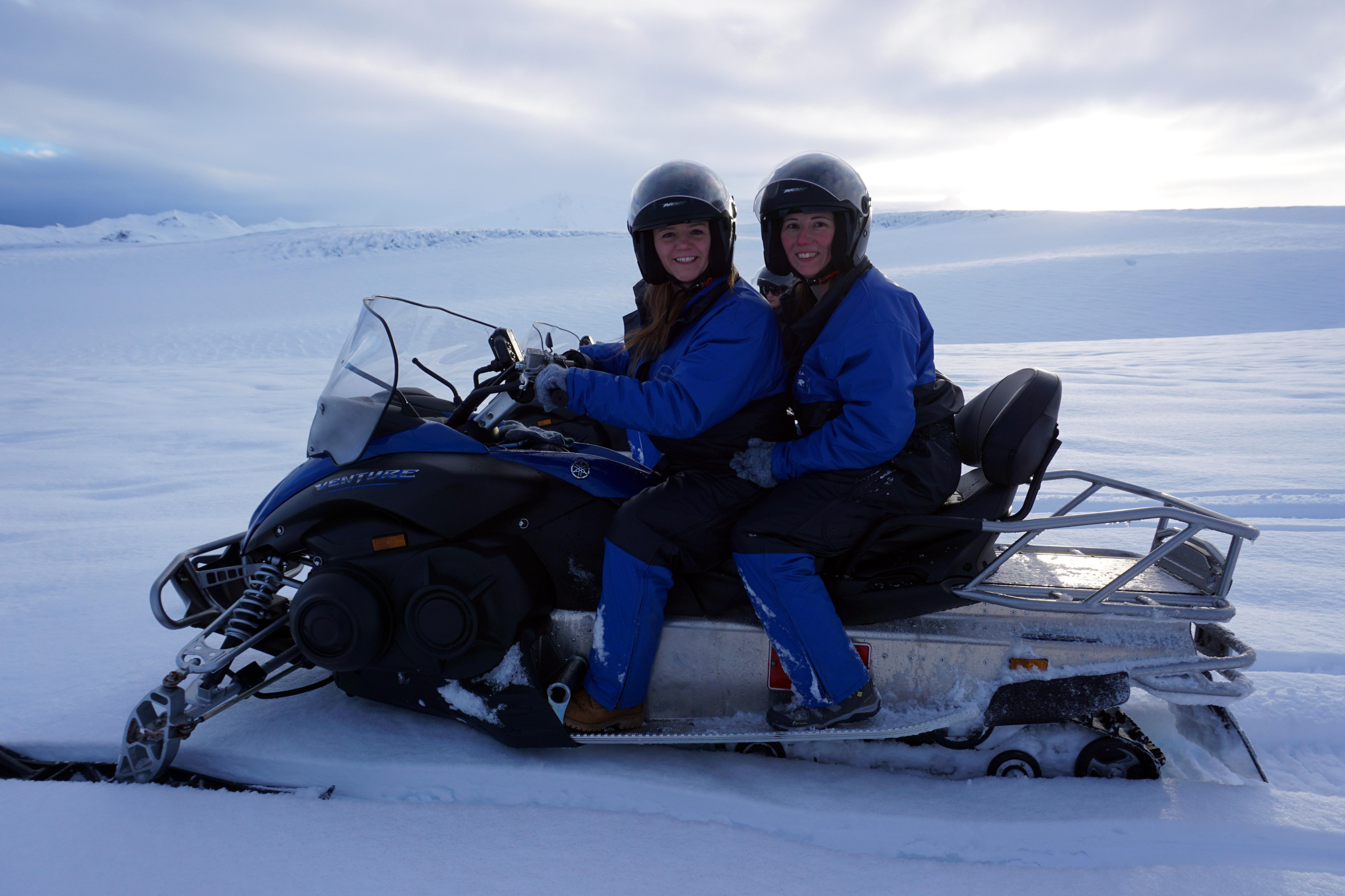 Two women atop a snowmobile on a Vatnajökull Glacier ice cave tour in Iceland