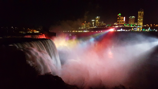 American Falls lit up at night viewed from Niagara Falls State Park in New York