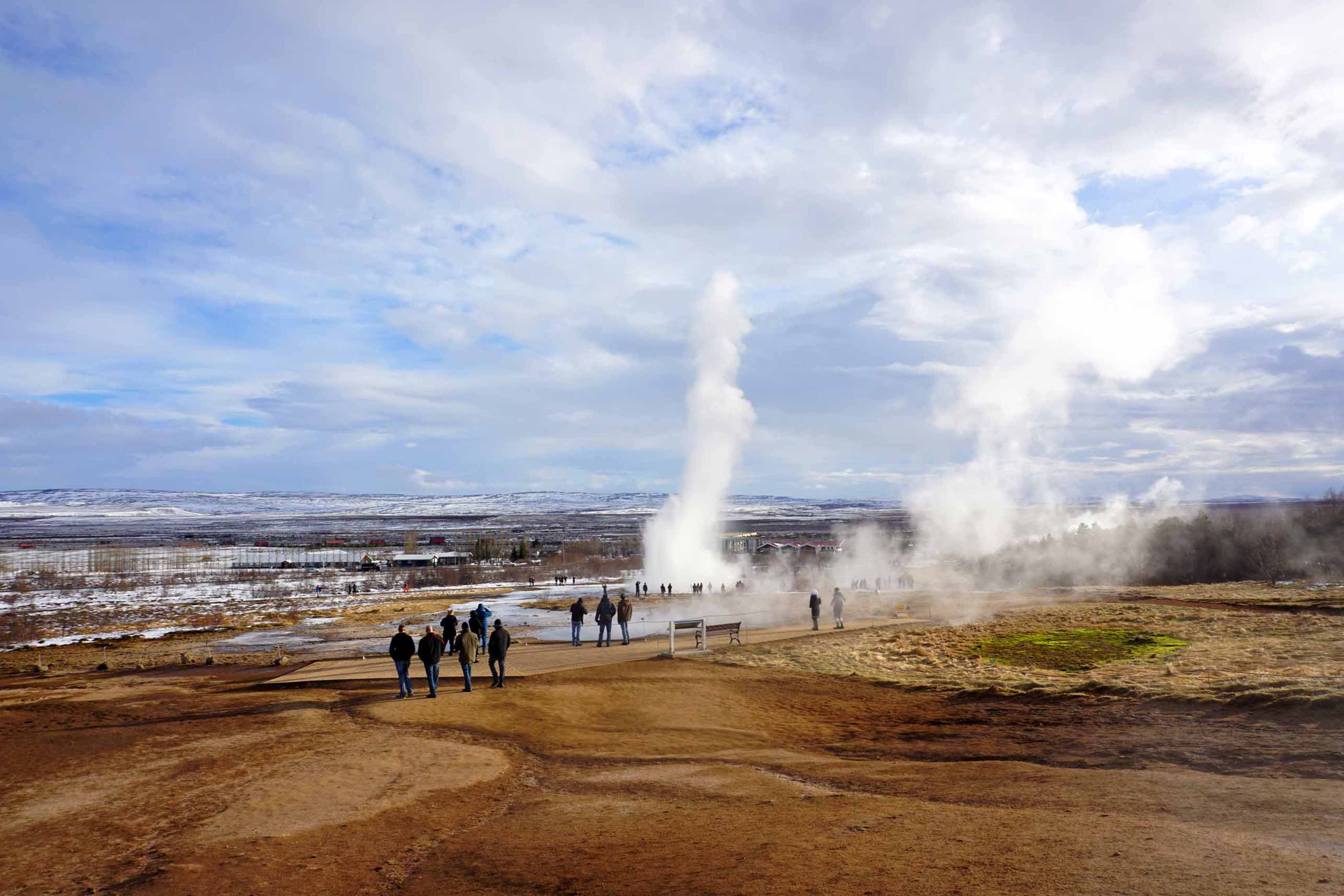 Steaming earth and an eruption of Strokkur geyser in the Geysir area, part of the Golden Circle in Iceland